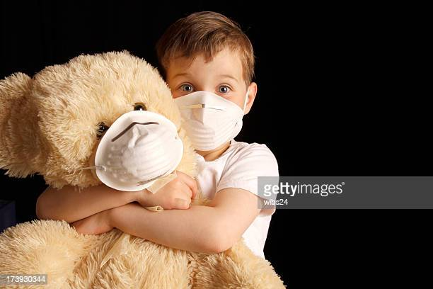 sick kid and teddy bear. - flu mask stock photos and pictures