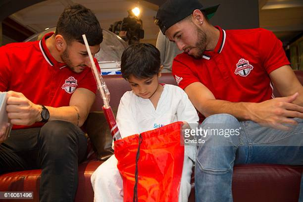 Sick Kids patient Ibrahim Khan checks out the contents of a lot bag brought by Toronto FC Chris Mannella left and Jonathan Osorio Members of Toronto...