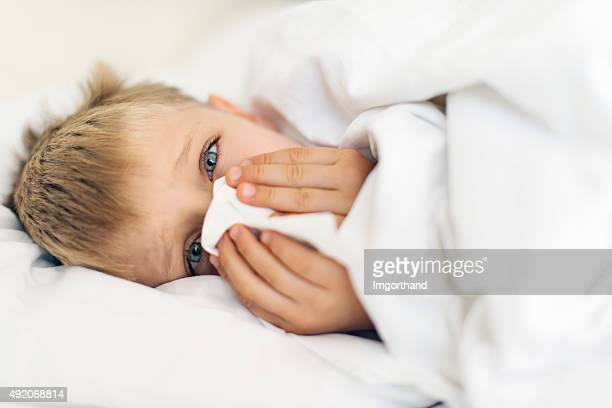 Sick little boy cleaning nose in bed