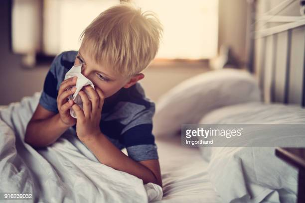 sick little boy lying in bed and blowing nose - cold virus stock pictures, royalty-free photos & images