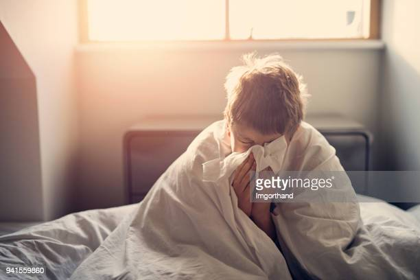 sick little boy lying in bed and blowing nose - infectious disease stock pictures, royalty-free photos & images