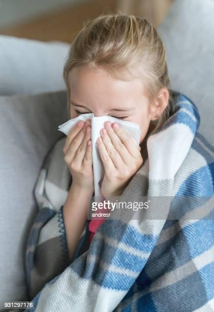 niña enferma en la casa soplar su nariz mientras que cubrió con un edredón - sonarse fotografías e imágenes de stock