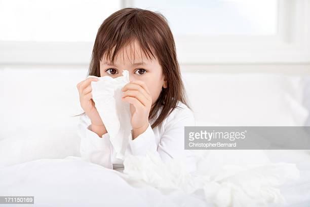 小さな女の子は彼女の病気の鼻をかむのベッド