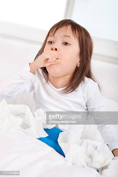 sick little girl coughing in bed - coughing stock photos and pictures