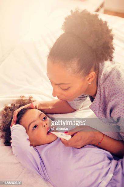 sick little girl having her body temperature measured - hot body girls stock photos and pictures