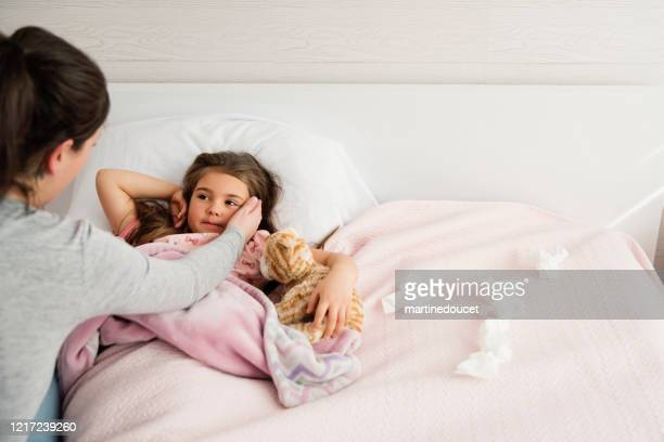 """sick little girl lying in bed with mother comforting her. - """"martine doucet"""" or martinedoucet stock pictures, royalty-free photos & images"""