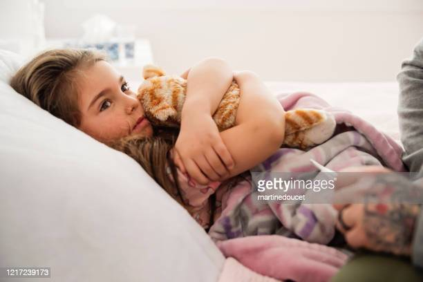 """sick little girl lying in bed with thermometer. - """"martine doucet"""" or martinedoucet stock pictures, royalty-free photos & images"""