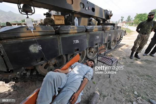 A sick local resident receives medical treatment while lying on a bench alongside an armoured vehicle as a Pakistani soldier looks on in the village...