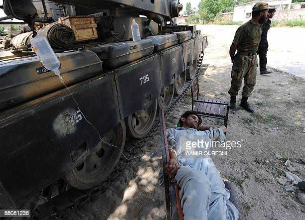A sick local resident receives medical treatment while lying on a bench alongside an armoured vehicle near a Pakistani army base in the village of...