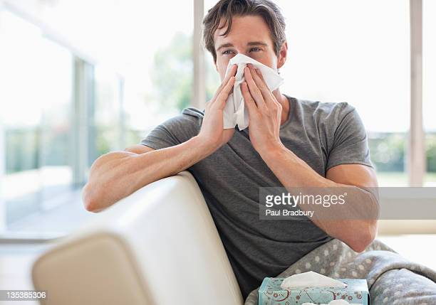 sick man blowing his nose - pneumonia stock pictures, royalty-free photos & images
