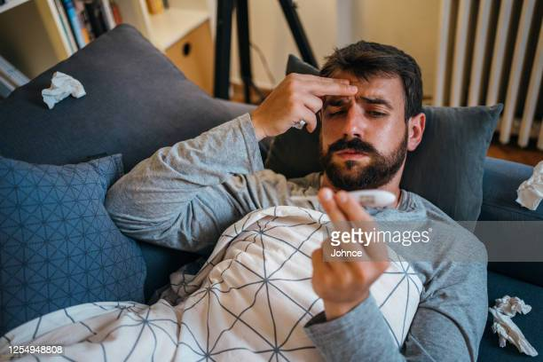 sick man checking the temperature - symptom stock pictures, royalty-free photos & images
