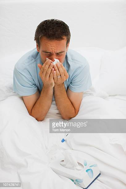 Sick man in bed blowing nose
