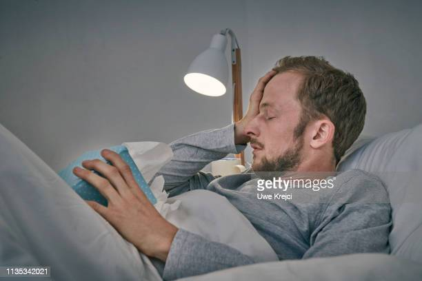 sick man in bed - fever stock pictures, royalty-free photos & images