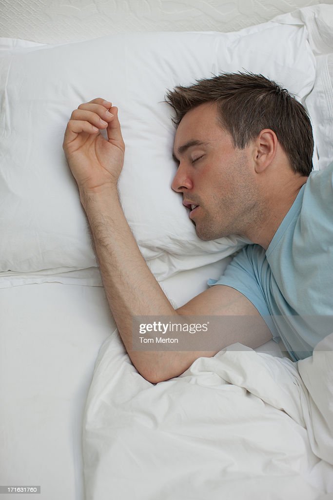 Sick man sleeping in bed : Stock Photo