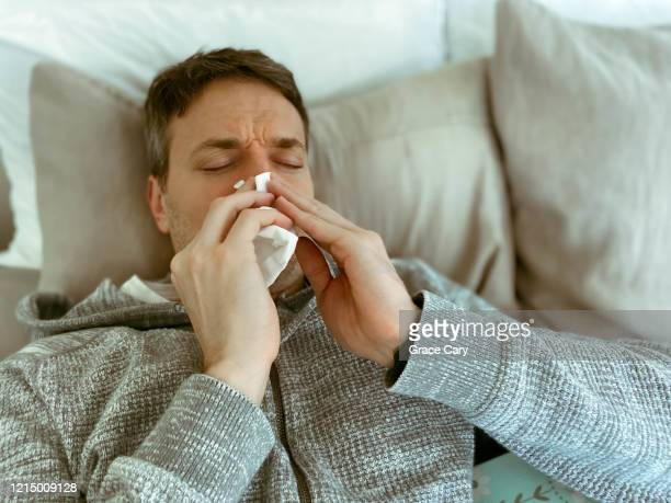 sick man sneezes in bed - blowing nose stock pictures, royalty-free photos & images