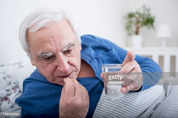 sick man taking tablets - taking a pill stock pictures, royalty-free photos & images