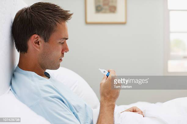 sick man taking temperature with digital thermometer - fever stock pictures, royalty-free photos & images