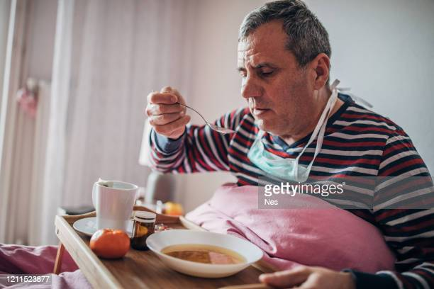 sick man uses eating soup in bed - recovery stock pictures, royalty-free photos & images