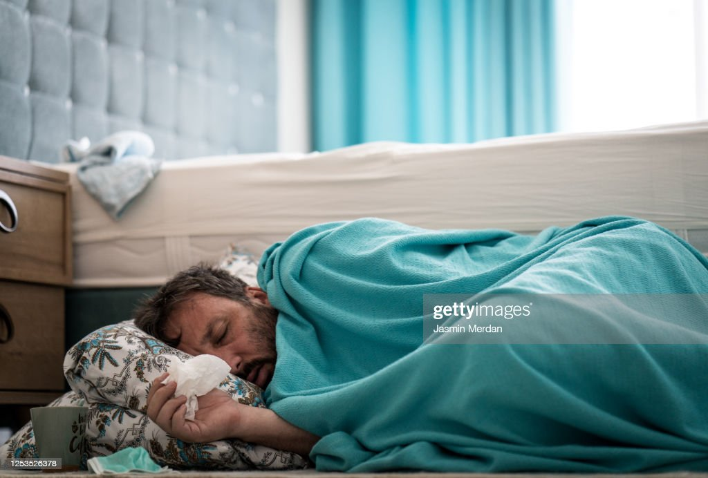 Sick man with fever on ground in bedroom : Stock Photo