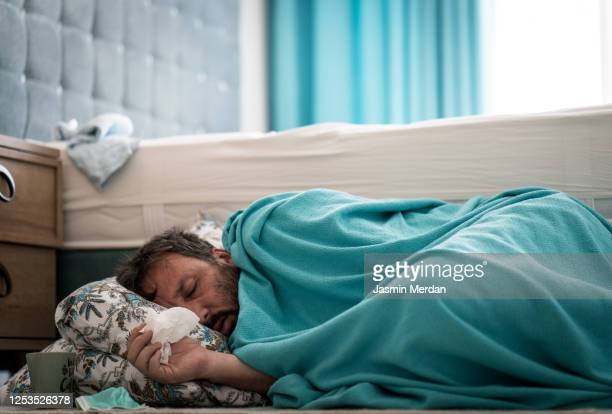 sick man with fever on ground in bedroom - cold and flu stock pictures, royalty-free photos & images