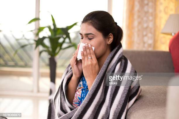 sick woman sitting at home blowing