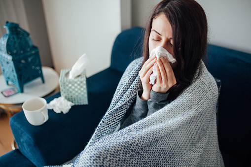 Sick woman blowing her nose, she covered with blanket 1135175362