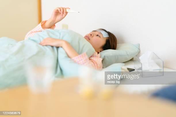 ベッドで休んでいる間に彼女の体温をチェックする病気の女性 - 発熱 ストックフォトと画像