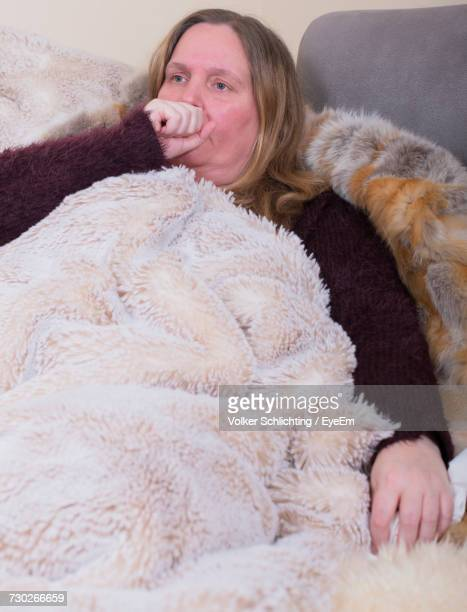 Sick Woman Coughing While Relaxing On Bed At Home