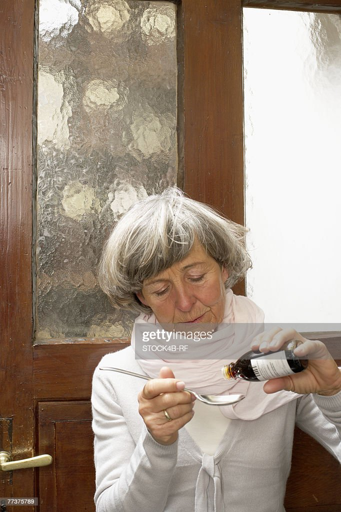 Sick woman drizzling medicine on a spoon : Photo