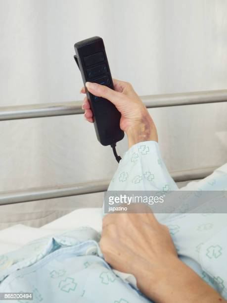 sick woman in a hospital bed adjusting bed height with remote control - streptomyces antibioticus stock photos and pictures