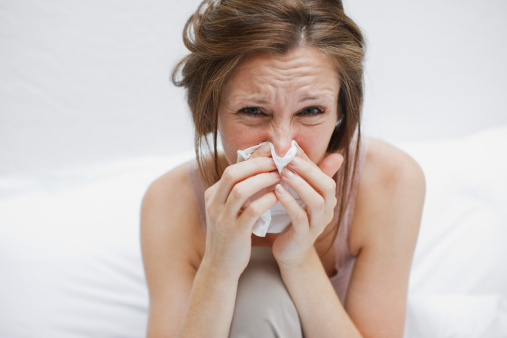 Sick woman in bed blowing nose - gettyimageskorea