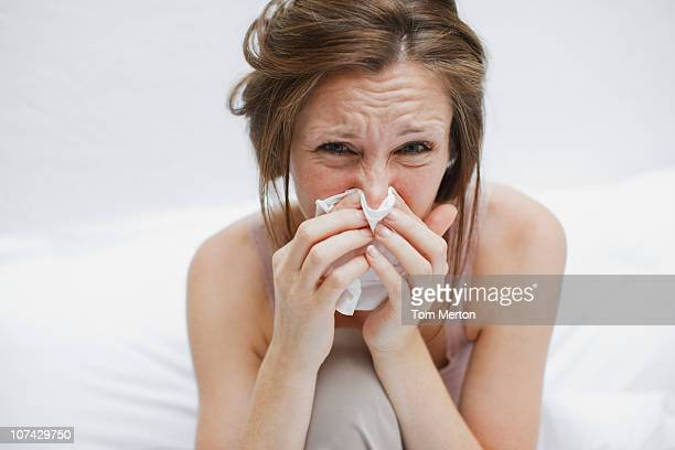 sick woman in bed blowing nose - pneumonia stock pictures, royalty-free photos & images