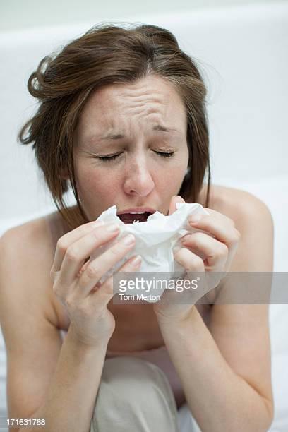 Mujer enferma sonarse en la cama