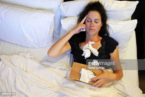 sick woman lay in bed - rafael ben ari foto e immagini stock