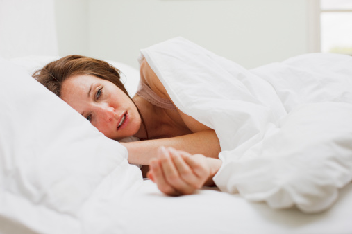 Sick woman laying in bed under blanket - gettyimageskorea