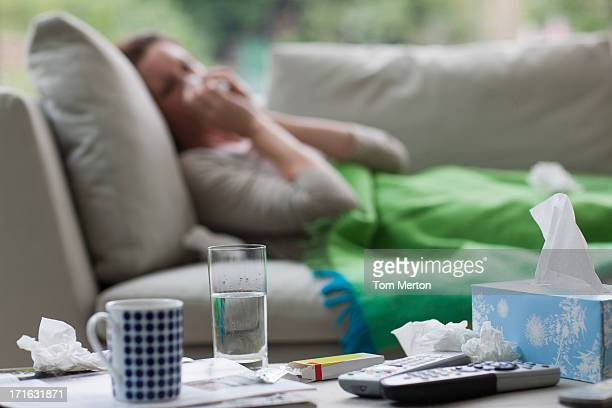 sick woman laying on sofa blowing nose - pneumonia stock pictures, royalty-free photos & images