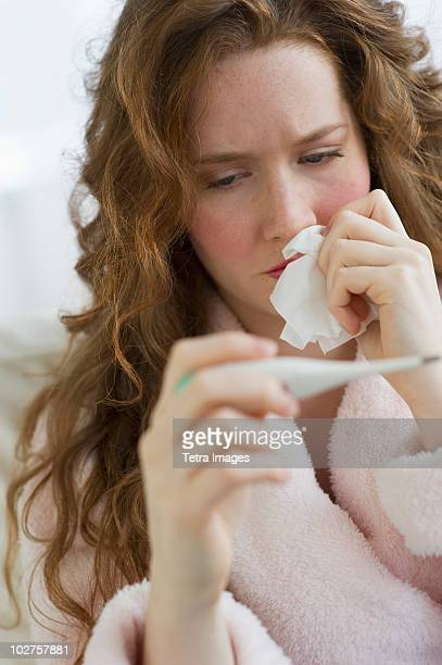 Sick woman looking at thermometer