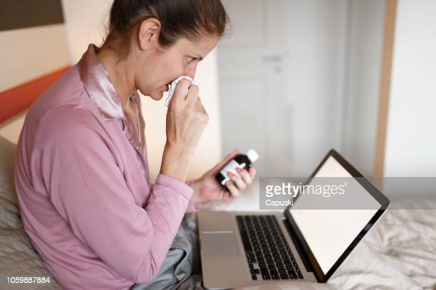 sick woman on bed video chatting with doctor on laptop - telemedicine stock photos and pictures