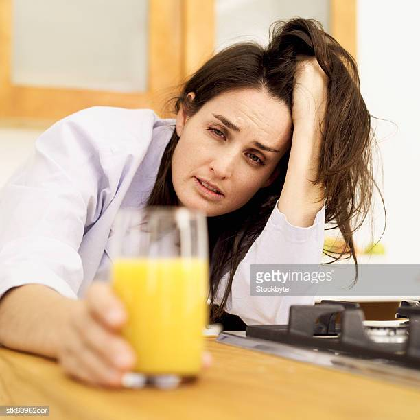 sick woman reaching for a glass of orange juice
