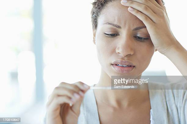 sick woman taking her temperature - fever stock pictures, royalty-free photos & images