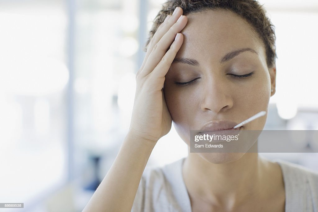 Sick woman taking her temperature : Stock Photo