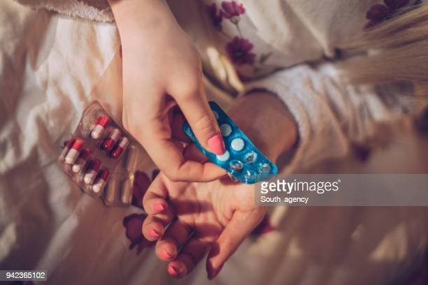sick woman taking painkillers - taking a pill stock pictures, royalty-free photos & images