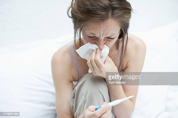Kranke Frau, die Temperatur mit Digitales thermometer und Schnäuzen