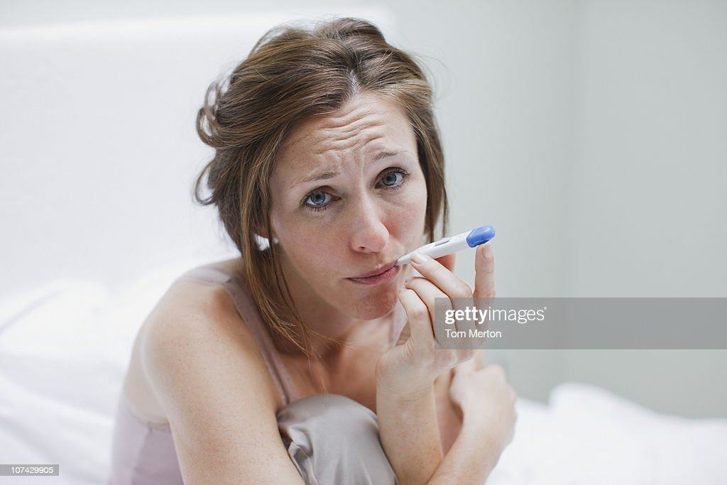 Sick woman taking temperature with digital thermometer : Stock Photo