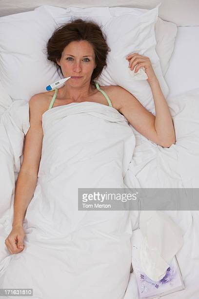 Sick woman taking temperature with digital thermometer