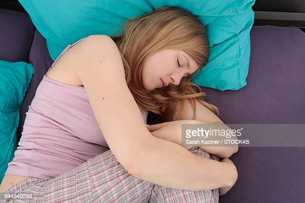 sick woman writhing in bed - fetal position stock photos and pictures