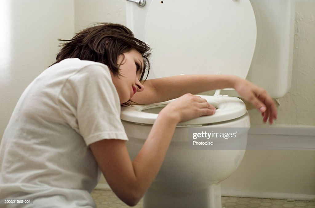 Sick young woman leaning on toilet bowl : Stock Photo