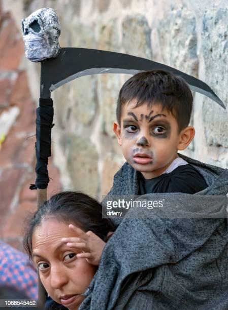 Faucille-carying garçon et sa grand-mère au Día de los Muertos Festival à Oaxaca