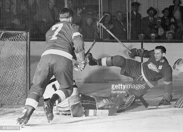 Sid Abel Detroit Red Wings captain makes a mighty swing and throws himself of balance in the hockey game against the Boston Bruins while falling he...