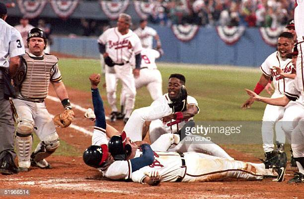 Sid Bream gets hugged by teammate David Justice after Bream scored the winning run in the bottom of the ninth, to clinch the National League...